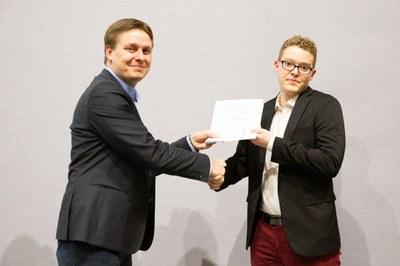 Patrick Schneider vom Debeka Innovation Center überreicht den IT-Förderpreis an Alexander Nilles. Bild: Henry Tornow.