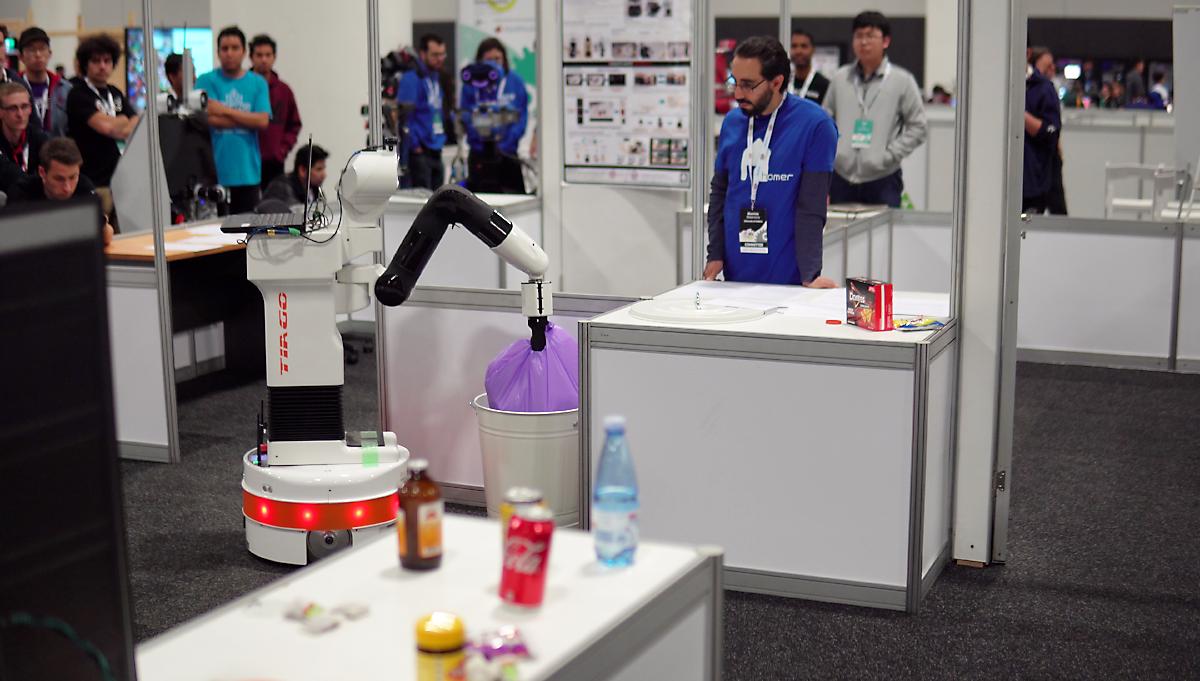 Roboter TIAGo beim Robocup 2019 in Sydney hebt einen Müllsack aus dem Mülleimer und bringt ihn nach draußen. Foto: Tem