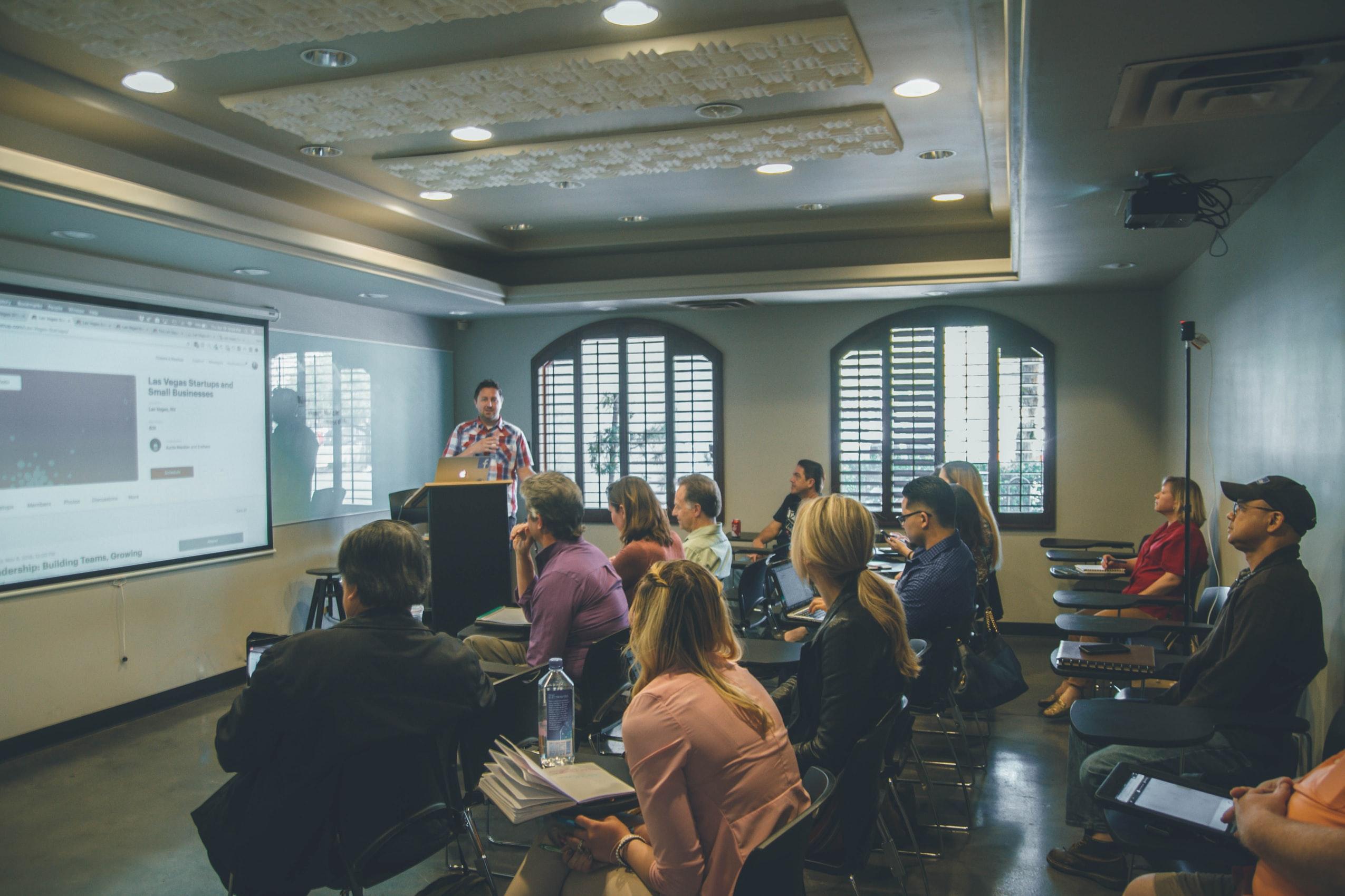Eine Gruppe von etwa 12 Menschen hört in einem Seminarraum einen Vortrag