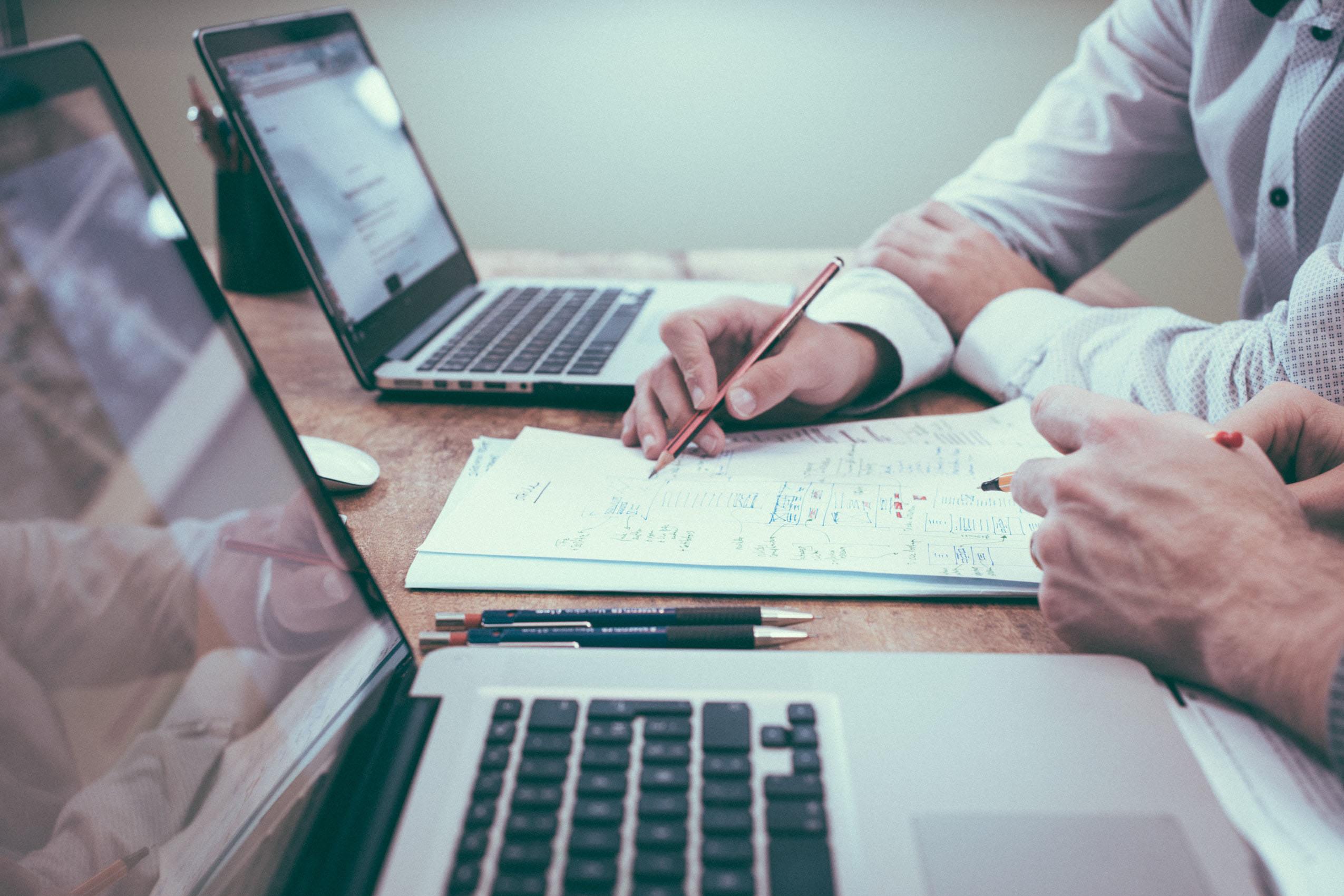 Ein Tisch mit zwei Laptops und Unterlagen, zwei Menschen brarbeiten ein Arbeitsblatt