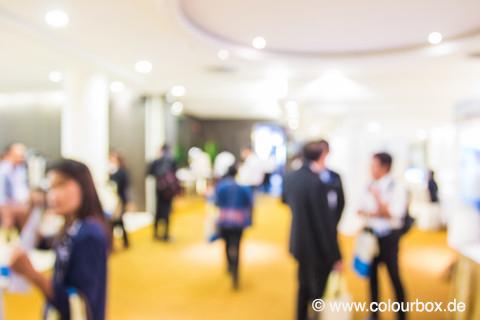 Bild zeigt eine Halle mit Menschen die sich unterhalten.