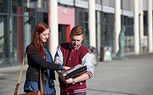 Zwei Studierende auf dem Campusgelände Koblenz. Im Hintergrund die Bibliothek.