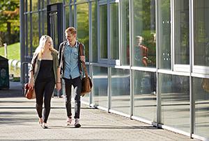 Zwei Studierende laufen über das Campusgelände in Koblenz und unterhalten sich.