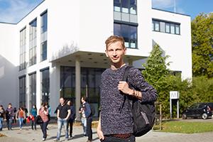 Blick auf Gebäude M - davor Studierende
