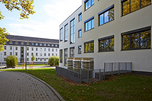 Blick auf das A-Gebäude auf dem Campus Koblenz, vorbei am M-Gebäude im Vordergrund.