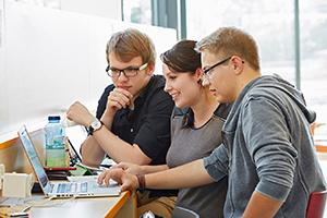 Lernsituation mit drei Studierenden am Laptop in der Menseria Koblenz.