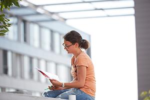 Lernende Studentin. Im Hintergrund Gebäude K.