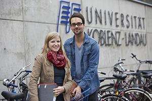 Studierende vor dem Logo der Universität